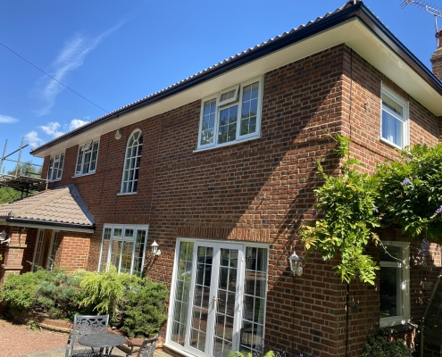 White Fascias and Soffits with Black Seamless Aluminium Gutters in Leatherhead Surrey 1
